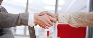 Svar-Life-Science-business-people-shaking-hands-closing-a-business-deal-computer-in-the-background
