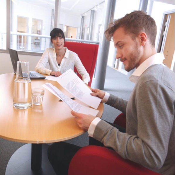 Svar-Life-Science-two-business-people-sitting-down-to-negotiate-business-deal-in-scandinavian-style-office