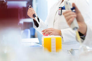 Svar-Life-Science-blurred-image-of-female-and-male-hand-holding-pipettes-yellow-boxes-in-foreground